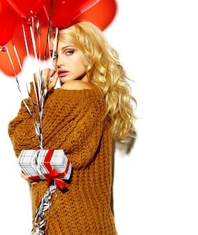 Zoete blonde model poseren met heden en hart ballonnen