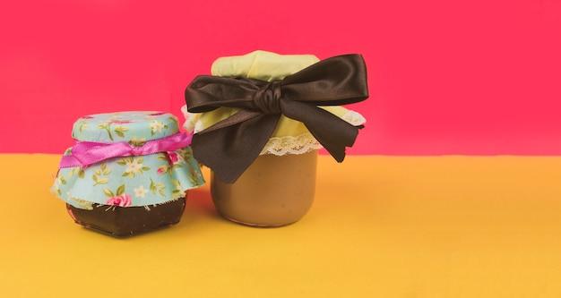 Zoete braziliaanse melk en gelei binnen op pot die op gekleurde achtergrond wordt geïsoleerd. pasteltrend in frisse kleuren. ruimte voor tekst.