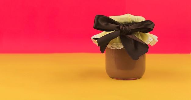 Zoete braziliaanse melk en gelei binnen op pot die op gekleurde achtergrond wordt geïsoleerd. pasteltrend in frisse kleuren.
