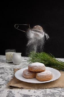 Zoete broodjes bestrooid met poedersuiker. het concept van thuis bakken voor kerstmis