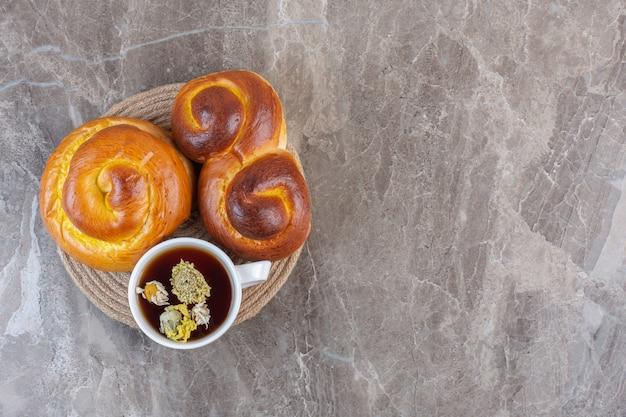 Zoete broodjes en een kopje thee op een onderzetter op marmer.