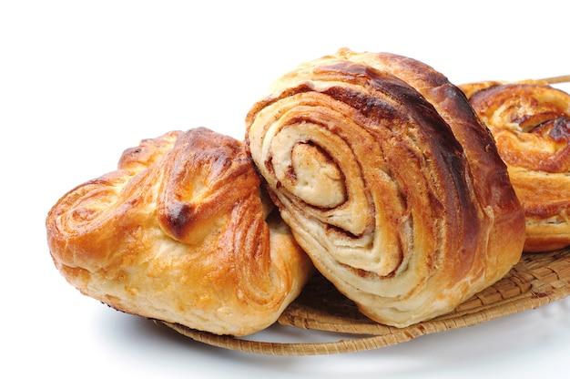 Zoete broodjes in houten plaat op wit