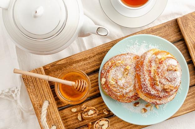 Zoete broodjes met walnoten, geraspte kokosnoot en honing op een houten dienblad