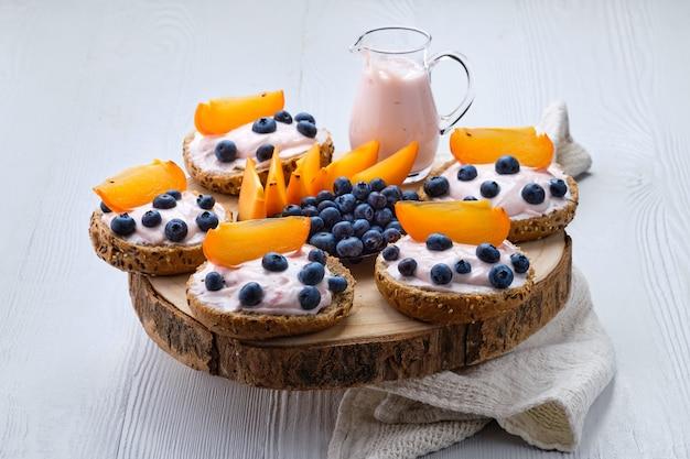 Zoete broodjes met zachte kaas, bosbessen en plak van persimmon op witte houten tafel