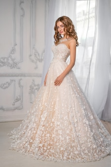 Zoete bruid in jurk bij het raam, gelukkige vrouw