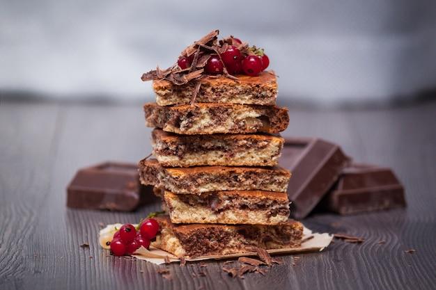 Zoete cake met cacaopoeder en bessen op donkere houten achtergrond