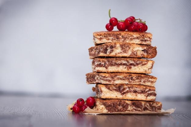 Zoete cake met cacaopoeder zebra met bessen en chocolade op donkere houten achtergrond. kopieer ruimte