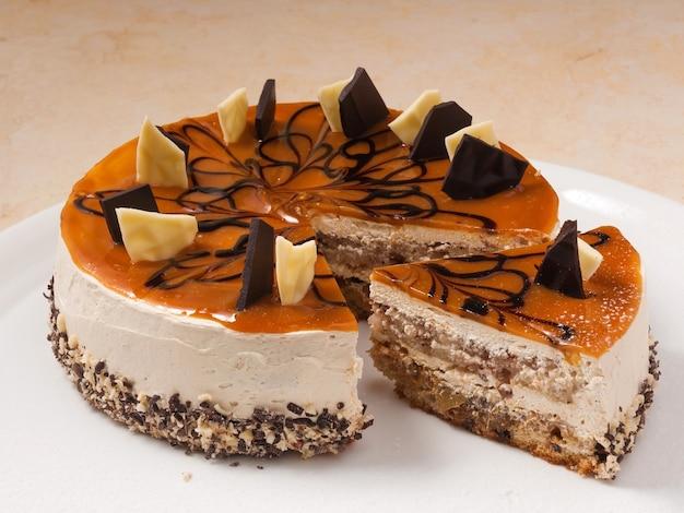 Zoete cake met karamel, noten en biscuitgebak met chocoladedecoratie