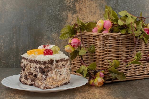 Zoete cake met mand met rozen op marmeren tafel