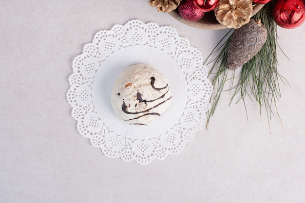 Zoete cake op plaat en kerstmisspeelgoed op witte oppervlakte