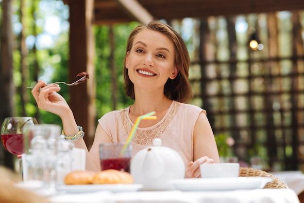 Zoete cake. stralende stijlvolle vrouw, gekleed in modieuze blouse zoete cake zittend in het restaurant eten