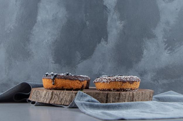 Zoete chocolade donuts op stuk hout op stenen oppervlak