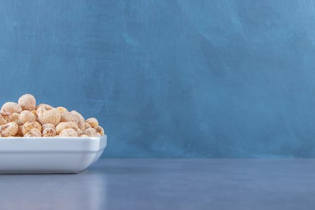 Zoete cornflakes met muesli in een kom, op de marmeren tafel.