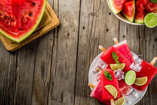 Zoete de zomerwatermeloen en kalkijslollys met gesneden watermeloen en munt, op witte marmeren achtergrondexemplaarruimte