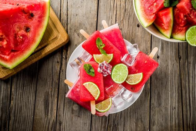 Zoete de zomerwatermeloen en limoenijslollys met gesneden watermeloen en munt, op witte marmeren lijst