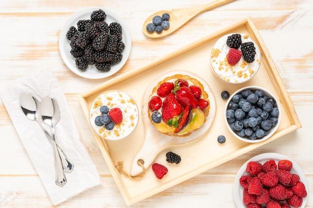 Zoete desserts met verse bessen op houten.