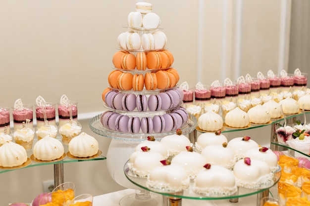 Zoete desserttafel of candybar. tafel met verschillende snoepjes voor feest. vakantiebuffet met cupcakes en andere desserts. macaron, cupcakes, marshmallow close-up