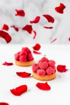 Zoete desserttartelettes met rode mousse hartjes erop, versierd met rode rozenblaadjes
