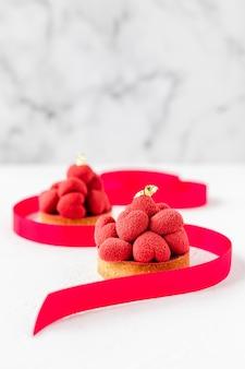 Zoete desserttartelettes met rode moussehartjes erop, versierd met een lint