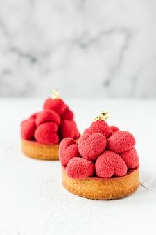 Zoete desserttartelettes met rode moussehartjes erop