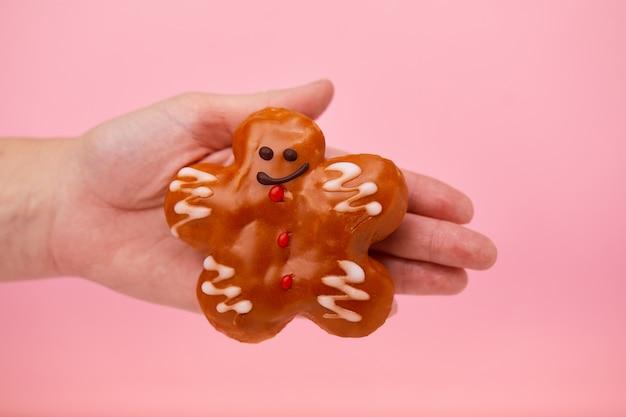 Zoete donuts, hand houdt een zoete donut vast in de vorm van een man.
