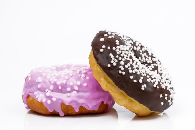 Zoete donuts in chocolade en lavendel glazuur op een wit. kopieer ruimte
