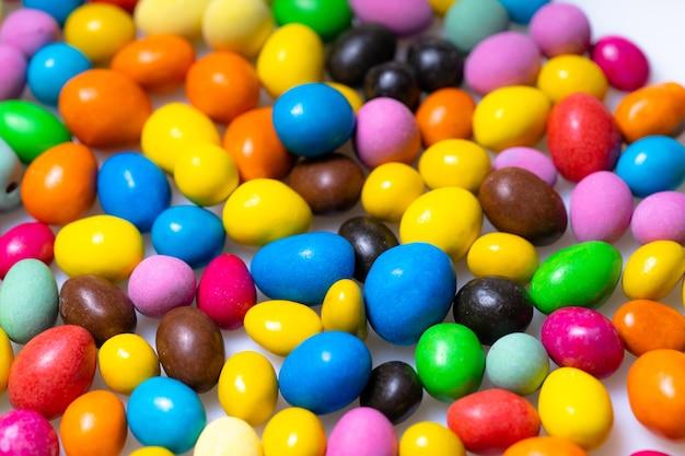 Zoete dragees snoepjes. het verspreiden van gebak decoratie achtergrond. kleurrijke ronde kleine taxi's.