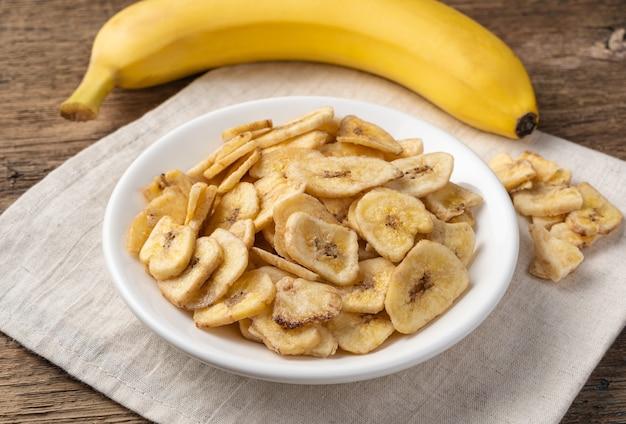 Zoete droge bananen met een witte plaat op een achtergrond van verse banaan. zijaanzicht, close-up.