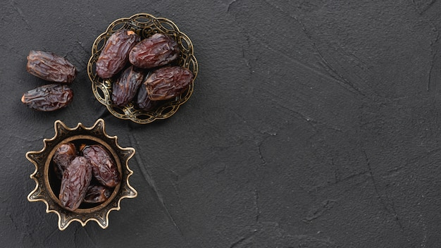 Zoete droge fruit dadels in de koperen stijlvolle metalen schaal op het zwarte oppervlak