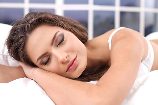 Zoete dromen. aantrekkelijke jonge vrouw in lingerie die in bed slaapt en glimlacht