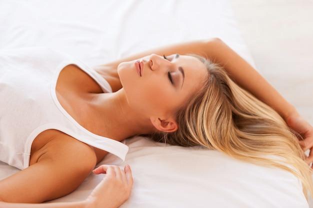 Zoete dromen. bovenaanzicht van mooie jonge vrouw in hemd liggend op bed en ogen gesloten houden