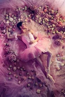 Zoete dromen. bovenaanzicht van mooie jonge vrouw in roze ballet tutu omgeven door bloemen. lentestemming en tederheid in koraallicht.