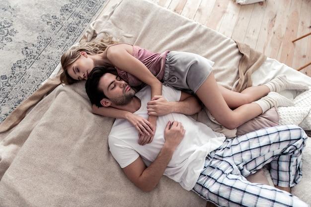 Zoete dromen. knappe donkerharige jonge man met een wit overhemd en zijn schattige blonde vrouw tot op het bed