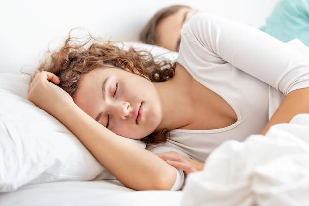 Zoete droom blanke paar slapen in een comfortabel bed thuis.