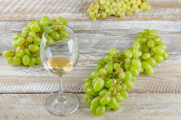 Zoete druiven met drankje op houten achtergrond, hoge hoekmening.