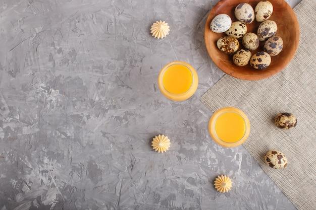 Zoete eierlikeur in glas met kwartelseieren en schuimgebakjes