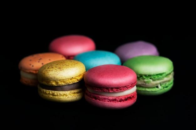 Zoete en kleurrijke franse bitterkoekjes op zwarte achtergrond