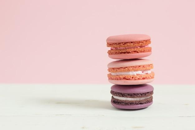 Zoete en kleurrijke franse makarons of macaron op witte houten lijst roze achtergrond, dessert.