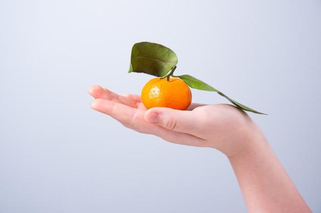 Zoete en sappige mandarijn in de hand van een kind op een grijze achtergrond. vooraanzicht