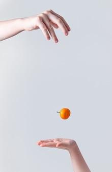 Zoete en sappige mandarijn valt van de ene hand naar de hand van een kind op een grijze achtergrond. vooraanzicht