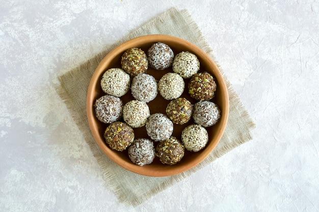 Zoete energieballen met noten en gedroogd fruit in het bovenaanzicht van de kleiplaat op grijze achtergrond