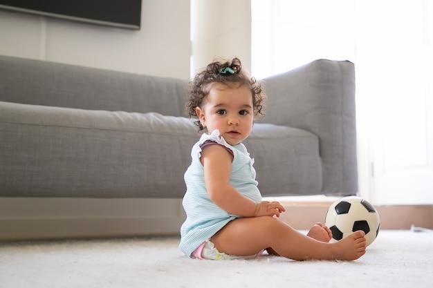 Zoete ernstige zwartharige babymeisje in lichtblauwe kleren, zittend op de vloer met voetbal, een. zijaanzicht. kid thuis en concept kindertijd