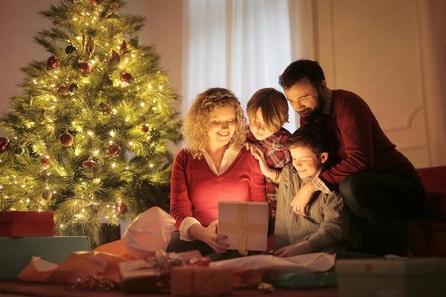 Zoete familie die kerstmisgiften in de avond opent