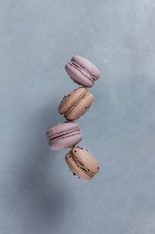Zoete franse bitterkoekjes vallen in beweging op een grijze ondergrond. pastelkleurige vliegende bitterkoekjes. voedsel, culinair en kookconcept