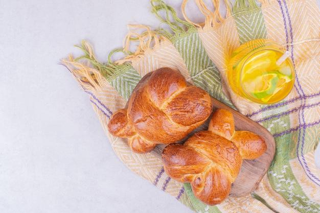 Zoete gebakjebroodjes op houten schotel met een glas limonade.