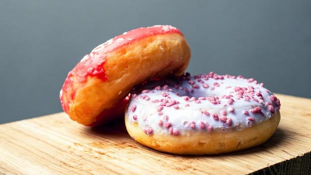 Zoete geglazuurde donuts op een houten bord. ronde koffiebroodjes.