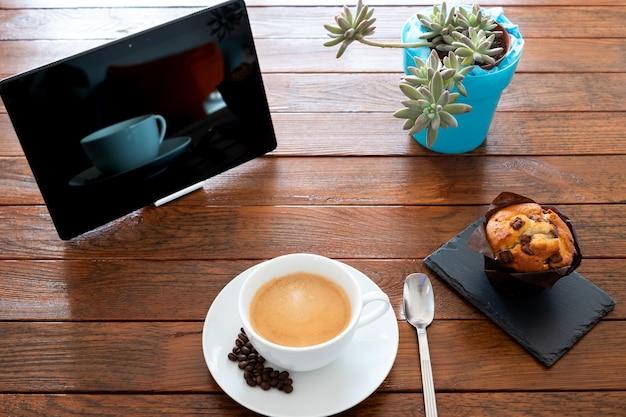 Zoete goedemorgen op een houten tafel bereid met een warme koffie en een chocolade cupcake. tablet en een plant