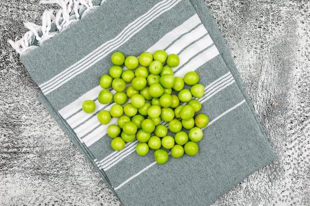 Zoete groene pruimen op een grunge oppervlak en picknick doek. plat lag.
