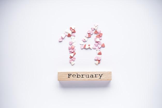Zoete harten en houten kalender op een witte achtergrond, plat leggen