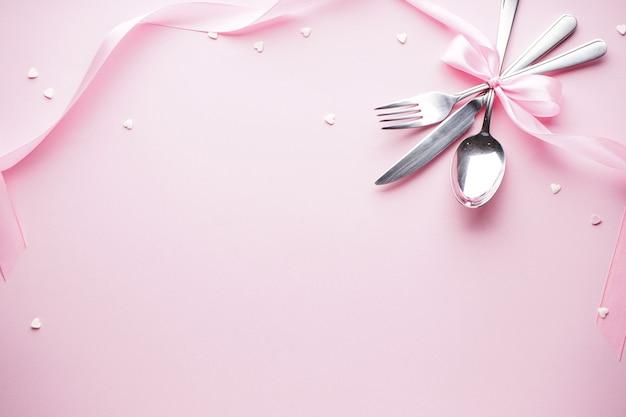 Zoete hartjes en bestek op een witte plaat met een roze lint op een roze achtergrond, plat leggen. valentijnsdag. moederdag achtergrond. liefde concept.